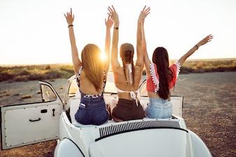 As jovens sentados em um carro