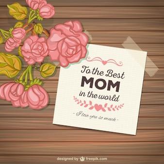 As mães Cartão do dia com as flores no fundo de madeira