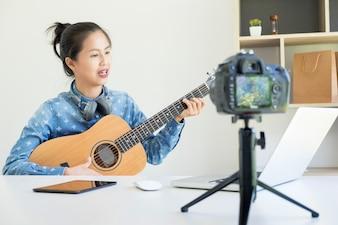 As mulheres cantam uma música com guitarra nas mãos usam câmera para transmitir vídeo ao vivo para redes sociais pela internet em casa.