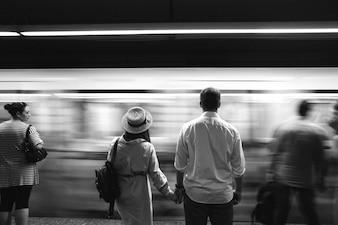 As pessoas se prendem mutuamente as mãos diante do trem subterrâneo