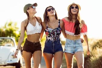 As raparigas que riem com shorts e óculos de sol