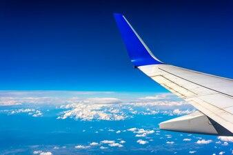 Asa do avião que voa acima das nuvens