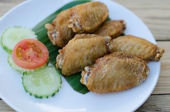 Asas de frango frito no prato branco