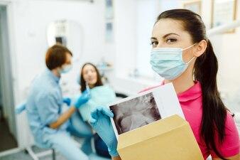 Assistente com máscara que mostra um raio-x