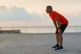 Atleta grave recuperando a respiração depois de correr
