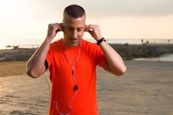 Atleta masculino confiante colocando fones de ouvido