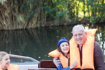 Avô alegre e neto vestida com coletes salva-vidas laranja