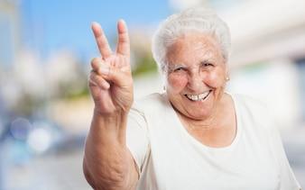 Avó com dois dedos levantados e sorrindo