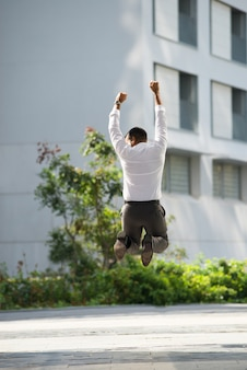 Back View of Businessman Raising Arms and Jumping