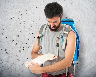 Backpacker curando um ferido sobre fundo branco