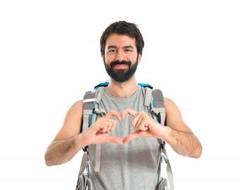 Backpacker fazendo um coração com as mãos sobre fundo branco