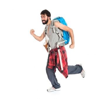 Backpacker jovem correndo sobre fundo branco