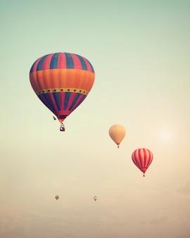 Balão de ar quente do vintage que voa no céu com névoa - estilo retro do efeito do filtro