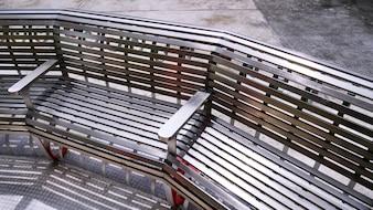 Banco curvo de aço inoxidável sob luz solar