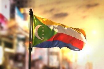 Bandeira dos Comores contra a cidade Fundo borrado no amanhecer Luz de fundo