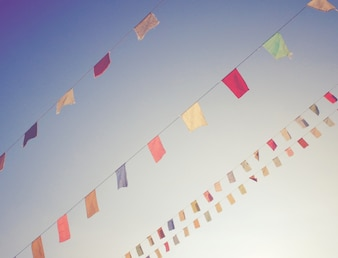 Bandeiras de bunting coloridas no céu azul com efeito de filtro retro