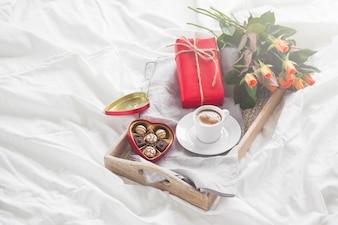Bandeja do pequeno almoço com um presente, flores e chocolates