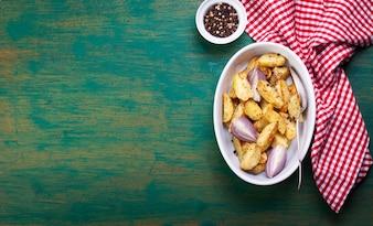 Batatas fritas em uma tigela e pimenta