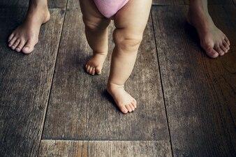 Bebê feliz aprendendo a caminhar com a mãe ajuda