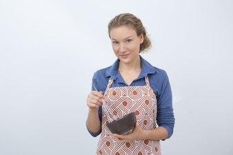 Bela dona de casa que chicoteia comida em uma tigela