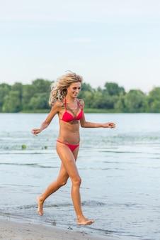 Bela garota loira correndo na praia
