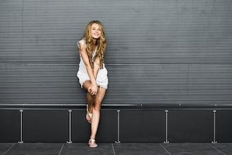 Bela garota loira perto da parede cinza