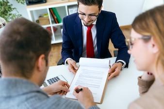 Bela jovem assinando contrato financeiro no escritório.
