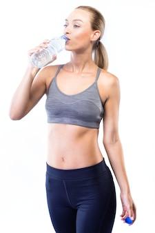 Bela jovem bebendo água depois de fazer exercício sobre fundo branco.