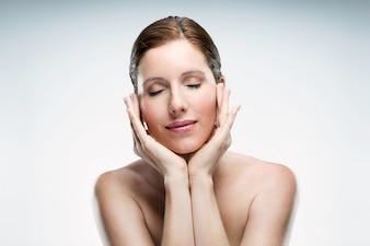 Bela jovem com pele saudável e olhos fechados posando isolado sobre fundo branco.