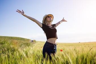 Bela jovem curtindo o verão em um campo.