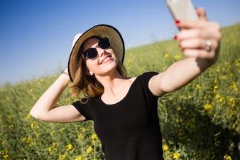 Bela jovem fazendo um selfie em um campo.