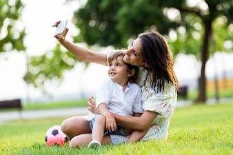 Bela jovem mãe com o filho que tira um selfie no parque.