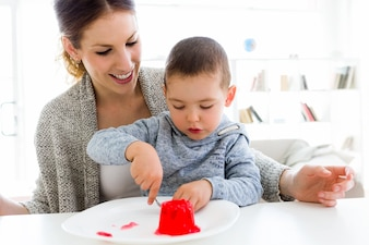 Bela jovem mãe e seu filho comendo geléia de morango em casa.