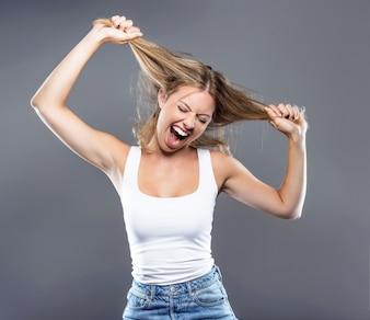 Bela jovem puxando o cabelo sobre fundo cinza.