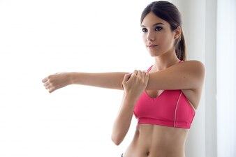 Bela jovem saudável fazendo exercícios em casa.