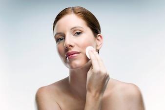 Bela jovem usando cosméticos sobre fundo branco.