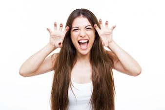 Bela moça gritando e rosnando como um animal sobre fundo branco.