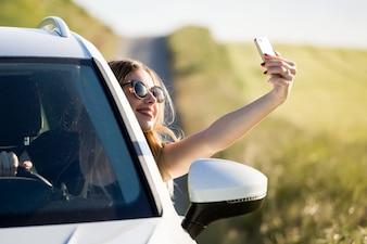 Bela moça tomando um selfie em um carro estacionado no campo.