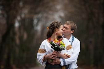 Bela noiva e noivo ucraniano em trajes de bordados nativos no fundo de árvores em um parque, cerimônia de casamento tradicional