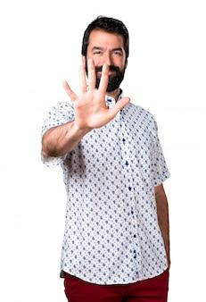 Belo homem moreno com barba contando cinco