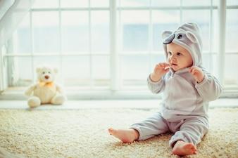 Belo menino sentado à beira da janela