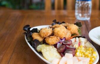 Bola de carne de camarão frito com molho doce na mesa de madeira.