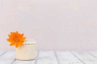 Branca superfície de madeira com vaso e flor de laranjeira