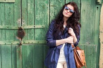 Brunette mulher com óculos de sol, segurando sua bolsa marrom