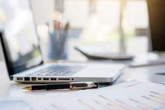Business desk com teclado, gráfico de relatório gráfico, caneta e tablet na mesa branca