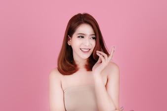 Cabelo curto, asiático, jovem, bonita, mulher, sorria e aponta sua cabeça, isolada sobre fundo rosa pastel. maquiagem natural, terapia SPA, cosmetologia, cosmetologia e conceito de cirurgia plástica