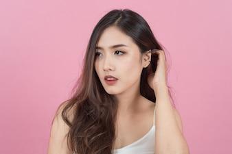Cabelo longo, asiática, jovem e bela, sorri e toca seu rosto, isolada sobre fundo rosa. maquiagem natural, terapia SPA, cosmetologia, cosmetologia e conceito de cirurgia plástica