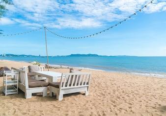 Cadeiras brancas e mesa na praia