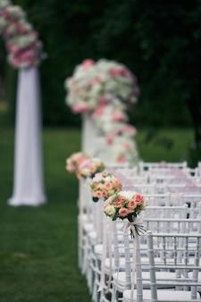 Cadeiras brancas estão nas fileiras no gramado verde