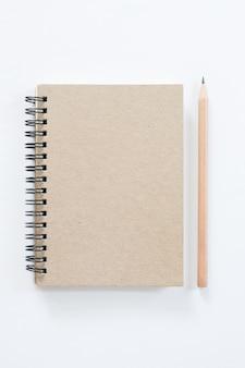 Caderno com lápis no fundo branco